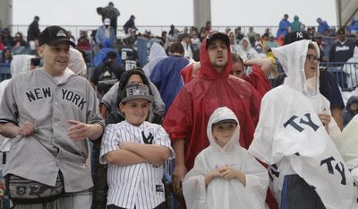 Rain gear-covered New York Yankees fans wait above the Yankees dugout before the Yankees final spring exhibition baseball game, against the Miami Marlins, was canceled due to heavy rain in Tampa, Fla., Saturday, March 29, 2014. (AP Photo/Kathy Willens)