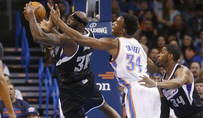 Sacramento Kings forward Reggie Evans (30) grabs a rebound in front of Oklahoma City Thunder center Hasheem Thabeet (34) and Sacramento's Jason Thompson (34) in the first quarter of an NBA basketball game in Oklahoma City, Friday, March 28, 2014. (AP Photo/Sue Ogrocki)