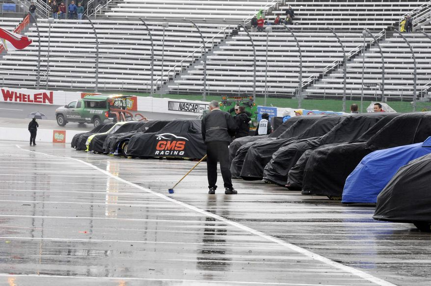 Trucks sit on pit road under covers as a crew member sweeps water from a pit stall during a rain delay for a NASCAR Truck Series auto race at Martinsville Speedway in Martinsville, Va., Saturday, March 29, 2014. (AP Photo/Mike McCarn)