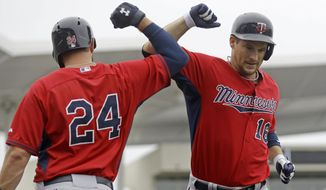 Minnesota Twins' Josh Willingham (16) is greeted by Trevor Plouffe (24) after hitting a solo home run during the second inning of an exhibition baseball game against the Boston Red Sox in Fort Myers, Fla., Saturday, March 29, 2014. (AP Photo/Gerald Herbert)