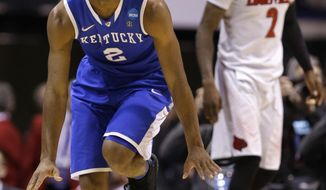 Kentucky's Aaron Harrison celebrates after making a three-point basket in front of Louisville's Russ Smith during the second half of an NCAA Midwest Regional semifinal college basketball tournament game Saturday, March 29, 2014, in Indianapolis. (AP Photo/Michael Conroy)