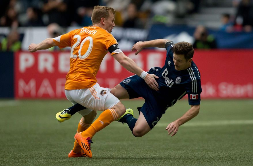Houston Dynamo's Andrew Driver, left, of England, and Vancouver Whitecaps' Jordan Harvey collide during the first half of an MLS soccer game in Vancouver, British Columbia, Saturday, March 29, 2014. (AP Photo/The Canadian Press, Darryl Dyck)