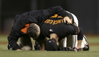 San Francisco Giants pitcher Tim Lincecum, right, is tended to by trainer Dave Groeschner after being struck by a ball hit by Oakland Athletics' Daric Barton during the fourth inning of an exhibition baseball game in San Francisco, Friday, March 28, 2014. (AP Photo/Jeff Chiu)