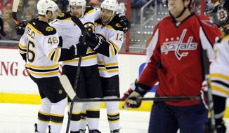 Boston Bruins right wing Jarome Iginla (12) celebrates his goal against the Washington Capitals with David Krejci (46), of the Czech Republic, and Andrej Meszaros (41) during the second period of an NHL hockey game, Saturday, March 29, 2014, in Washington. (AP Photo/Nick Wass)