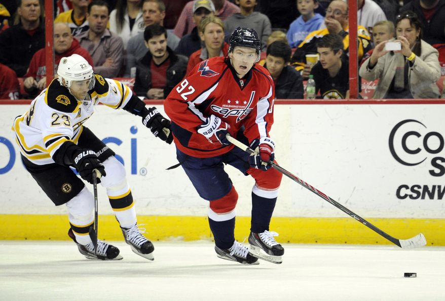 Washington Capitals center Evgeny Kuznetsov (92), of Russia, works the puck up ice against Boston Bruins center Chris Kelly (23) during the first period of an NHL hockey game, Saturday, March 29, 2014, in Washington. (AP Photo/Nick Wass)