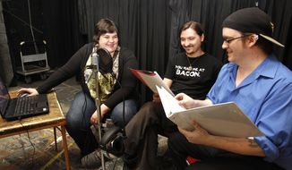 In this photo taken on Tuesday, March 18, 2014, assistant director Caitlin Hurban, left, laughs along with David Harnois, center, the voice of Sherlock Holmes, as Jens Petersen, right, the voice of Dr. Watson, stumbles over a line during a rehearsal of the three record readings of Sherlock Holmes at the Hope Martin Theatre in Waterloo, Iowa. (AP Photo/Waterloo Courier, Tiffany Rushing)