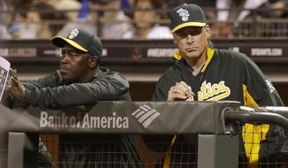 Oakland Athletics manager Bob Melvin, right, and batting coach Chili Davis watch from the dugout during the third inning of a spring exhibition baseball game against the San Francisco Giants in San Francisco, Friday, March 28, 2014. (AP Photo/Jeff Chiu)