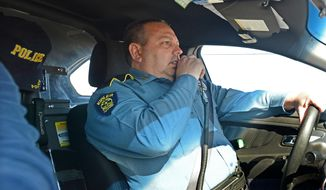 Kibler Police Chief Roger Green calls in a license plate before a traffic stop in Kibler on Tuesday, Feb. 25, 2014. (AP Photo/The Southwest Times Record, Brian D. Sanderford)