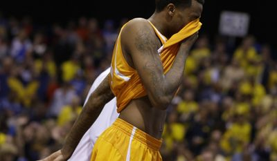 Tennessee's Jordan McRae wipes his face as he walks off the court after an NCAA Midwest Regional semifinal college basketball tournament game against the Michigan Friday, March 28, 2014, in Indianapolis. Michigan won 73-71.(AP Photo/Michael Conroy)