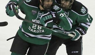 North Dakota forward Stephane Pattyn (28) is congratulated by forward Rocco Grimaldi (19) after Pattyn scored a goal against Ferris State in the second period of a regional final of the NCAA men's college hockey tournament, Saturday, March 29, 2014, in Cincinnati. (AP Photo/Al Behrman)
