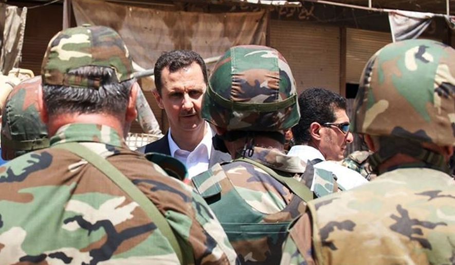 Syrian President Bashar Assad talking with soldiers with during Syrian Arab Army day in Darya, Syria. (AP Photo/Syrian Presidency via Facebook, File)
