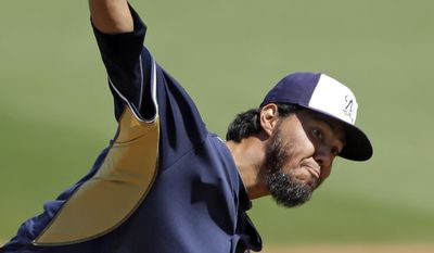 Milwaukee Brewers starting pitcher Yovani Gallardo delivers against the Cleveland Indians in the first inning of a spring exhibition baseball game Wednesday, March 26, 2014, in Goodyear, Ariz. (AP Photo/Mark Duncan)