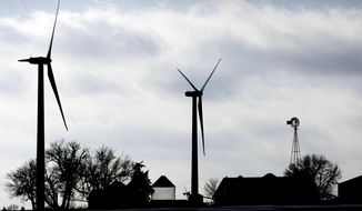 FILE - In this Dec. 30, 2008 file photo, two wind turbines stand near a traditional windmill on a farm near Mount Carmel, Iowa. The Iowa Senate passed bills to triple the amount of solar energy tax credits available to farmers, homeowners, and businesses and to extend the deadline to complete wind turbine projects and still qualify for a tax break. (AP Photo/Charlie Neibergall, File)