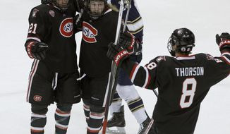 St. Cloud State forward Brooks Bertsch (21) celebrates with teammates Joey Benik, center, and Cory Thorson (8) after scoring against Notre Dame goaltender Steven Summerhays during the first period of an NCAA West college regional hockey game in St. Paul, Minn., Saturday, March 29, 2014. (AP Photo/Ann Heisenfelt)