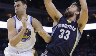 Memphis Grizzlies' Marc Gasol (33) scores next to Golden State Warriors center Andrew Bogut during the first half of an NBA basketball game Friday, March 28, 2014, in Oakland, Calif. (AP Photo/Marcio Jose Sanchez)