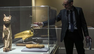 "In this March 20, 2014 photo, Brooklyn Museum, Egyptian, Classical and Ancient Middle Eastern Art, curator, Edward Bleiberg points to an ibis coffin, that is displayed as part of the exhibit ""Soulful Creatures: Animal Mummies in Ancient Egypt,"" at the Orange County's Bowers Museum in Santa Ana, Calif. The exhibition is on the ancient the mummification of animals in the Egyptian culture and religion. Drawn from the renowned collections of the Brooklyn Museum, Soulful Creatures features choice examples from among the many millions of mummies of birds, cats, dogs, snakes, and other animals preserved from at least thirty-one different cemeteries throughout Egypt. (AP Photo/Damian Dovarganes)"