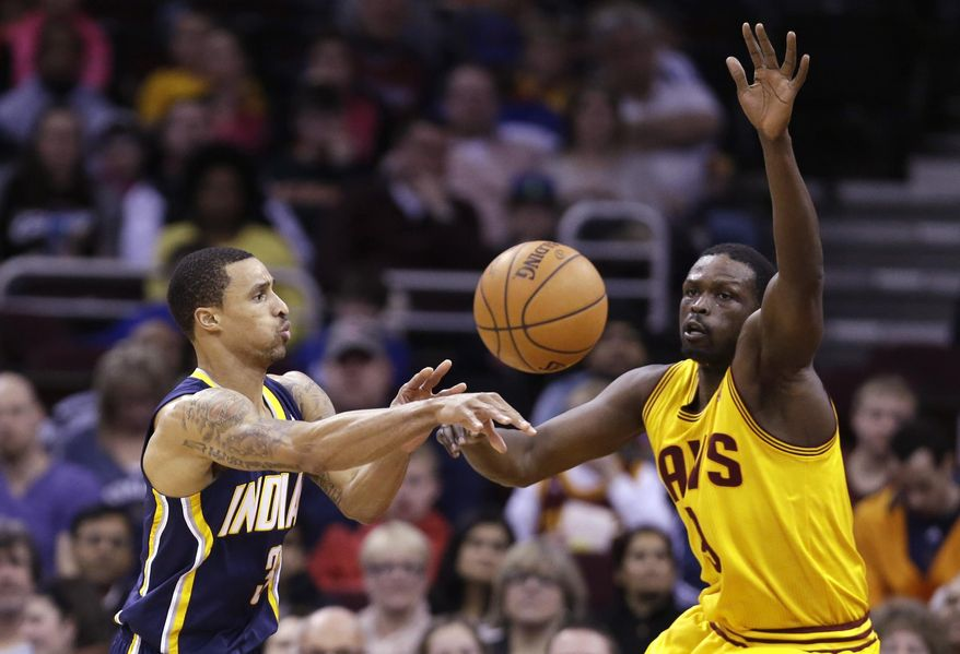 Indiana Pacers' George Hill, left, passes against Cleveland Cavaliers' Luol Deng, from Sudan, during the second quarter of an NBA basketball game Sunday, March 30, 2014, in Cleveland. (AP Photo/Tony Dejak)