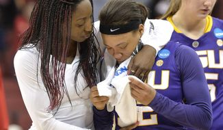 LSU assistant coach Tasha Butts, left, embraces Danielle Ballard following their loss to Louisville in a regional semifinal game at the NCAA women's college basketball tournament, Sunday, March 30, 2014, in Louisville, Ky. Louisville defeated LSU 73-47. (AP Photo/Timothy D. Easley)