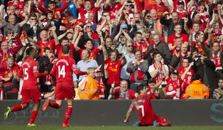Liverpool's Luis Suarez , right, celebrates after scoring against Tottenham during their English Premier League soccer match at Anfield Stadium, Liverpool, England, Sunday March 30, 2014. (AP Photo/Jon Super)