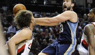 Memphis Grizzlies' Marc Gasol (33) shoots against Portland Trail Blazers' Robin Lopez, left, and LaMarcus Aldridge, right, during the first half of an NBA basketball game in Portland, Ore., Sunday March 30, 2014. (AP Photo/Greg Wahl-Stephens)