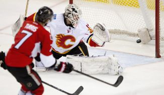Ottawa Senators Kyle Turris scores on Calgary Flames goalie Karri Ramo during second period NHL action Sunday March 30, 2014 in Ottawa, Ontario. (AP Photo/The Canadian Press, Adrian Wyld)