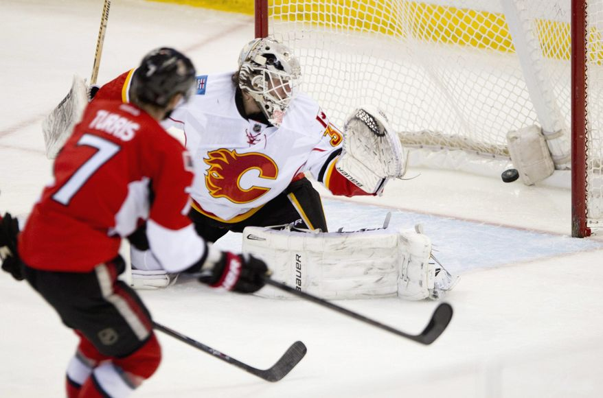 Ottawa Senators Kyle Turris scores on Calgary Flames goalie Karri Ramo during second period NHL action Sunday March 30, 2014 in Ottawa, Ontario. (AP Photo/The Canadian Press, Adrian Wyld)