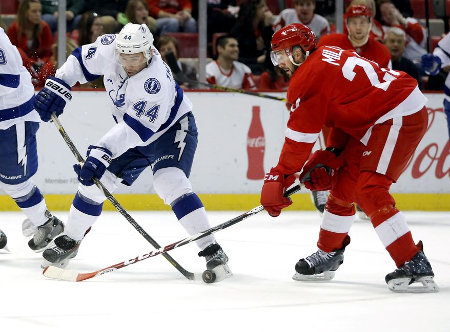 Tampa Bay Lightning's Nate Thompson (44) has his stick blocked by Detroit Red Wings' Drew Miller (20) while trying to take a shot on goal during the first period of an NHL hockey game, Sunday, March 30, 2014, in Detroit. (AP Photo/Duane Burleson)