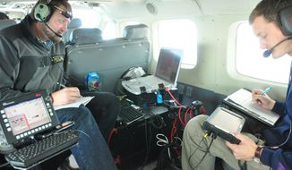 In this photo taken in October 2012, released by WSI, a Quantum Spatial Company,  sensor operators Lennie Rummel left, and Drew Wendeborn, right, are shown inside a helicopter taking measurements with LIDAR, a high-tech laser system mounted on the aircraft, to build a detailed elevation map of the terrain above Omak, Wash. The maps can be used by planners and homeowners to begin to assess landslide risk. (AP Photo/ WSI, a Quantum Spatial Company)