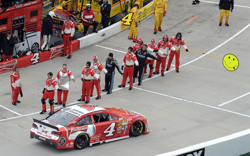 Kevin Harvick (4) pulls off pit road as his crew members wave before the start of a NASCAR Sprint Cup auto race at Martinsville, Speedway, Sunday, March 30, 2014, in Martinsville, Va. (AP Photo/Mike McCarn)