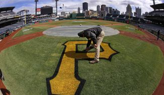 In this photo made with a fisheye lens, Derek Hurlburt, assistant field management supervisor at PNC Park, puts the finishing touches on the Pittsburgh Pirates logo behind home plate Sunday, March 30, 2014, in preparation for the Pittsburgh Pirates season opening baseball game, Monday, March 31 against the Chicago Cubs in Pittsburgh. (AP Photo/Gene J. Puskar)