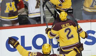 Minnesota forward Justin Kloos (25), defenseman Brady Skjei (2) and defenseman Justin Holl (12) celebrate after Kloos scored on St. Cloud State goalie Ryan Faragher during the first period of an NCAA West college regional hockey game in St. Paul, Minn., Sunday, March 30, 2014.  (AP Photo/Ann Heisenfelt)