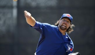 Toronto Blue Jays starting pitcher R.A. Dickey delivers a warmup pitch before starting in a spring training baseball game against the New York Yankees in Dunedin, Fla., Wednesday, March 26, 2014.  (AP Photo/Kathy Willens)