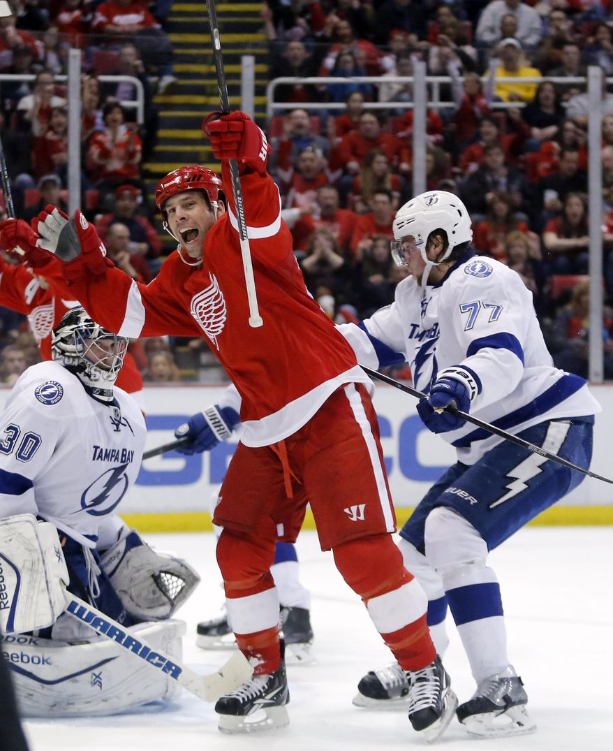 Detroit Red Wings' David Legwand, center, celebrates his goal against Tampa Bay Lightning's Ben Bishop (30) and Victor Hedman (77), of Sweden, during the second period of an NHL hockey game, Sunday, March 30, 2014, in Detroit. (AP Photo/Duane Burleson)