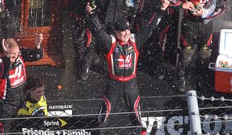 Driver Kurt Busch celebrates in victory lane after winning a NASCAR Sprint Cup auto race at Martinsville, Speedway in Martinsville, Va., Sunday March 30, 2014. (AP Photo/Steve Shappard)