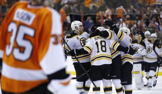 Boston Bruins' Reilly Smith (18) celebrates with teammates after scoring the game-winning goal against Philadelphia Flyers' Steve Mason (35) during a shootout in an NHL hockey game, Sunday, March 30, 2014, in Philadelphia. Boston won 4-3. (AP Photo/Matt Slocum)