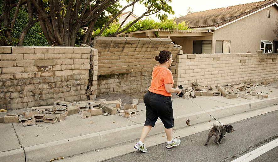 A woman walks her dog past a broken block wall in Fullerton, Calif., on Saturday, March 29, 2014,  after an earthquake hit Orange County Friday night. More than 100 aftershocks have rattled Orange County south of Los Angeles where a magnitude-5.1 earthquake struck Friday.  Despite the relatively minor damage, no injuries have been reported. (AP Photo/The Orange County Register, Ken Steinhardt)   MAGS OUT; LOS ANGELES TIMES OUT