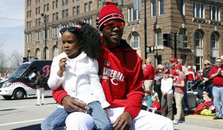 Cincinnati Reds closer Aroldis Chapman rides with his daughter Ashanti in the annual opening day parade, Monday, March 31, 2014, in Cincinnati. The Cincinnati Reds play the St. Louis Cardinals. (AP Photo/David Kohl)