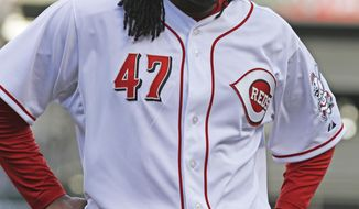 Cincinnati Reds starting pitcher Johnny Cueto walks off the field after giving up a home run to St. Louis Cardinals' Yadier Molina in the seventh inning of a baseball game, Monday, March 31, 2014, on opening day in Cincinnati. St. Louis won 1-0. (AP Photo/David Kohl)