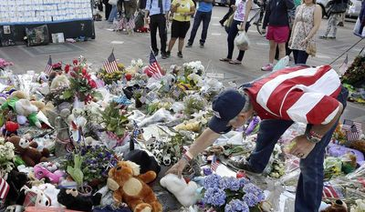** FILE ** In this May 7, 2013, file photo, Kevin Brown, of Boston, right, places a Teddy bear at a makeshift memorial to the victims of the April 15, 2013, bombings near the Boston Marathon finish line in Boston's Copley Square. (AP Photo/Steven Senne, File)