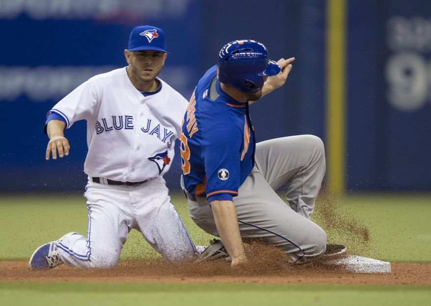 New York Mets' Daniel Murphy is tagged out by Toronto Blue Jays shortstop Jonathan Diaz while attempting to steal second base during sixth inning of an exhibition baseball game Saturday, March 29, 2014, in Montreal. (AP Photo/The Canadian Press, Paul Chiasson)
