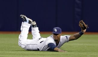 Tampa Bay Rays center fielder Desmond Jennings slides across the turf after making a first inning catch on a fly ball by Toronto Blue Jays' Jose Reyes during a baseball game Monday, March 31, 2014, in St. Petersburg, Fla. (AP Photo/Chris O'Meara)