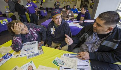 SEIU-UHW worker Refu Aguilera, right, assists Miguel Millan, 60, and his wife Alejandra,36, during a health care enrollment event at SEIU-UHW office, Monday, March 31, 2014, in Commerce, Calif.  Monday marks this year's open enrollment deadline, but consumers will get extra time to finish their applications.  (AP Photo/Ringo H.W. Chiu)