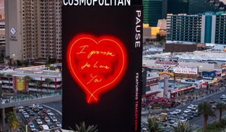"""This photo provided by The Cosmopolitan shows a giant LED sign that displays love notes outside The Cosmopolitan on the Las Vegas Strip. The casino plans to start broadcasting the animated works of contemporary British artist Tracey Emin for about three minutes every hour, starting on Monday, March 31, 2014. Passersby will see about a dozen giant indoor and outdoor marquees go black, then hand written phrases such as """"I promise to love ya"""" will appear in glowing letters. The Cosmopolitan says it's part of the casino's ongoing efforts to put interactive art in unexpected places, including the property's 65-foot-tall marquee. (AP Photo/The Cosmopolitan, Erik Kabik)"""