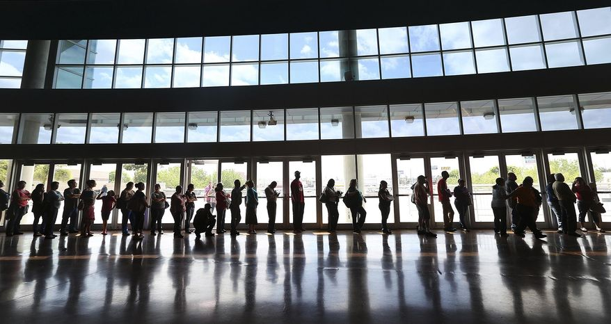 People line up to enroll for health insurance at the Alamodome in San Antonio, Texas on Monday, March 31, 2014.  The deadline is just hours away to sign up for insurance in the first enrollment period under President Barack Obama's signature health care law.  (AP Photo/San Antonio Express-News, Jerry Lara)  RUMBO DE SAN ANTONIO OUT; NO SALES