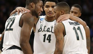 Michigan State's Branden Dawson, left, huddles with teammates Gary Harris, center, and Keith Appling in the first half of a regional final against Connecticut at the NCAA college basketball tournament on Sunday, March 30, 2014, in New York. (AP Photo/Seth Wenig)