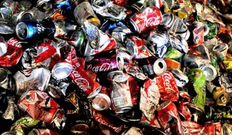 FILE - In this Feb. 11, 2014 file photo, thousands of empty and crushed soda cans build up on a conveyer belt near the end of the line at Tennis Sanitation in Saint Paul Park, Minn. Americans cut back on soda again in 2013, extending a trend that began nearly a decade ago. U.S. sales volume of carbonated soft drinks fell 3 percent in 2013, according to an annual report by Beverage Digest, an industry tracker.  (AP Photo/The St. Paul Pioneer Press, John Doman)  MINNEAPOLIS STAR TRIBUNE OUT