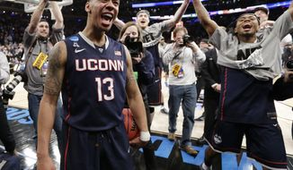 Connecticut's Shabazz Napier (13) celebrates after his team defeated Michigan State 60-54 in a regional final at the NCAA college basketball tournament, Sunday, March 30, 2014, in New York. Napier scored 17 points of his 25 points in the second half. (AP Photo/Frank Franklin II)