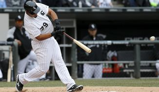 Chicago White Sox's Jose Abreu hits an RBI single off Minnesota Twins starting pitcher Ricky Nolasco, scoring Adam Eaton, during the third inning of an Opening Day baseball game Monday, March 31, 2014, in Chicago. (AP Photo/Charles Rex Arbogast)