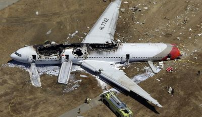 FILE - In this July 6, 2013 aerial file photo, the wreckage of Asiana Flight 214 lies on the ground after it crashed at the San Francisco International Airport, in San Francisco. Asiana Airlines says the Boeing 777 that crashed at San Francisco International Airport had inadequate warning systems to alert the crew to problems with air speed. In a filing with the National Transportation Safety Board released on Monday March 31, 2014, the airline says there was no indication that the plane's autothrottle had stopped maintaining the set air speed. (AP Photo/Marcio Jose Sanchez, file)