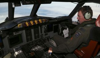 A Royal New Zealand Air Force  P-3 Orion's co-pilot and Squadron Leader Brett McKenzie controls the pane while  searching for the missing Malaysia Airlines Flight MH370 in the southern Indian Ocean, Monday, March 31, 2014. (AP Photo/Rob Griffith)
